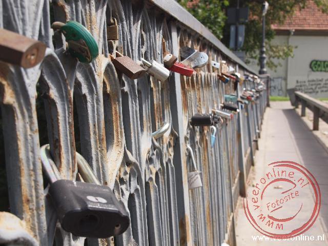 Bruidsparen bevestigen hun huwelijk door een slot aan de brug vast te maken en de sleutel in de rivier te gooien