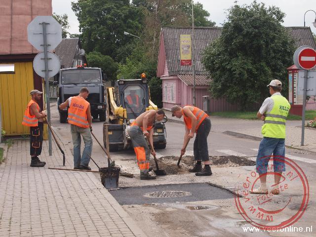 Met zes man wordt een stukje asfalt gedicht