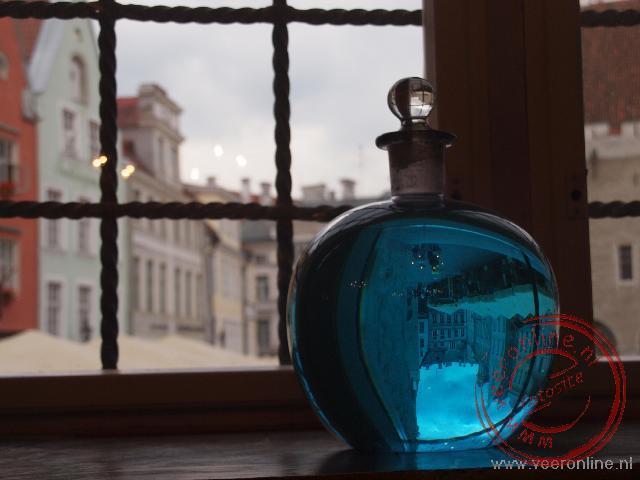 Het stadhuisplein weerspiegelt in het glas in de oude Apotheek