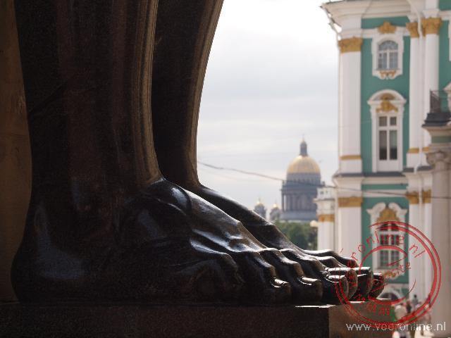De enorme voeten van de Atlanten beelden bij de Hermitage en op de achtergrond de Izäakskathedraal