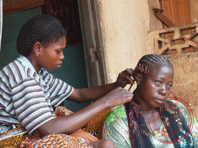 Het haar wordt ingevlochten op straat in Bassar