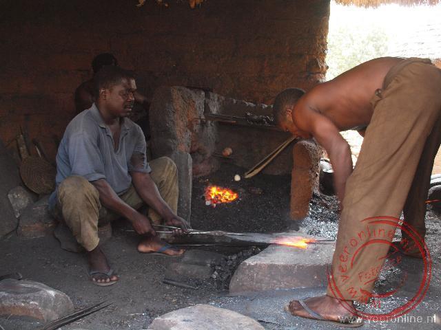 Met een grote steen wordt het heet gestookte ijzer in de gewenste vorm gebogen