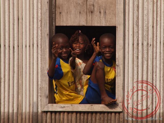 Kinderen kijken toe vanuit een raam van hun paalwoning