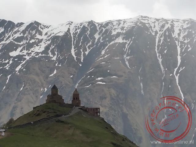 De Tsminda Sameba kerk voor de besneeuwde Mount Kasbek