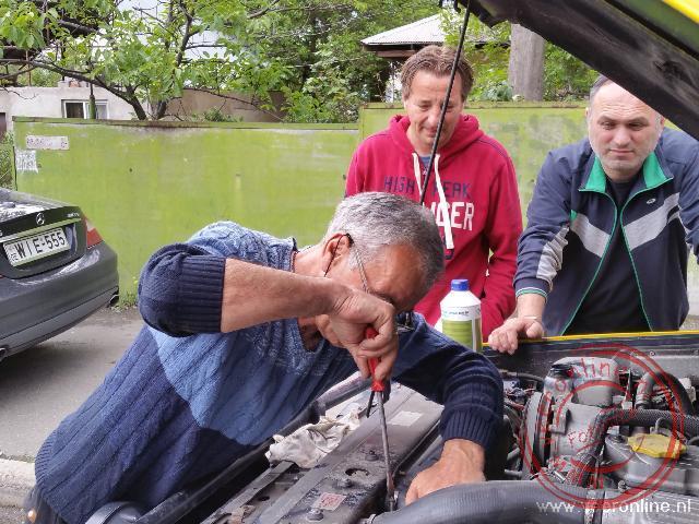 Een monteur probeert de koelvloeistof lekkage te verhelpen