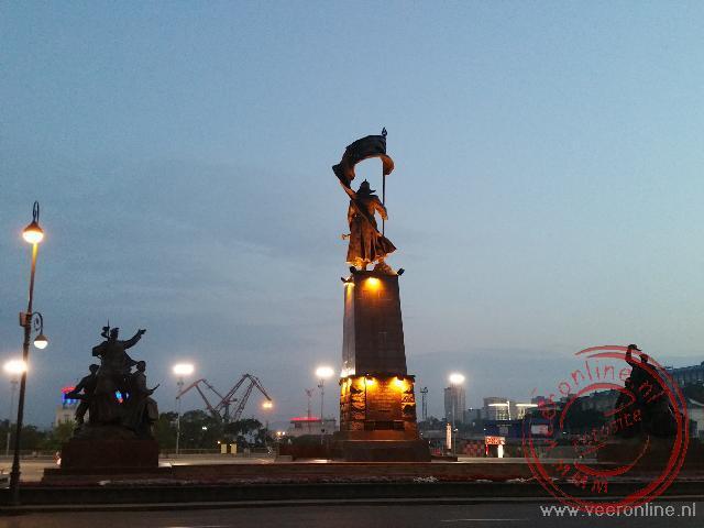 Het bronzen standbeeld van een soldaat met een vlag op het centrale plein is verlicht