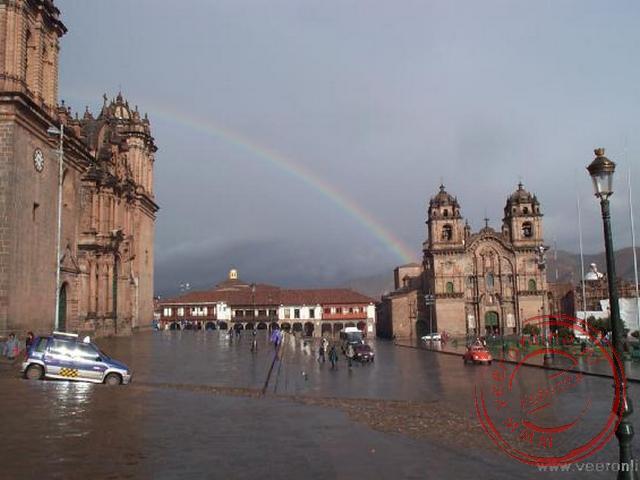 De regenboom op de Plaza de Armas. De regenboog staat van de Kathedraal (links) naar de Kerk de la Compania.