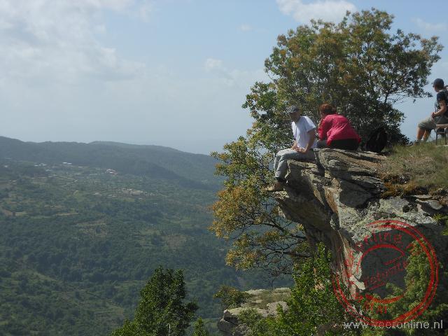 Rustig zitten op een overstekende rotspunt