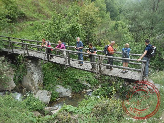 Onder de brug loopt een bergstroompje de vallei in