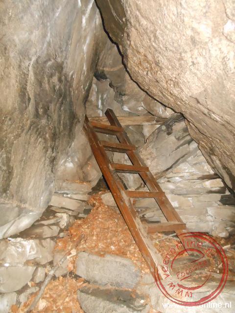 Een trappetje leidt naar een smalle doorgang in de grot