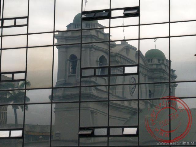 De kathedraal van San José weerspiegelt in één van de kantoorgebouwen