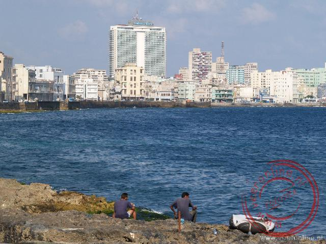 Vissers vissen in de zee met op de achtergrond de hoogbouw van hotels in de wijk Vedado langs de Malecón