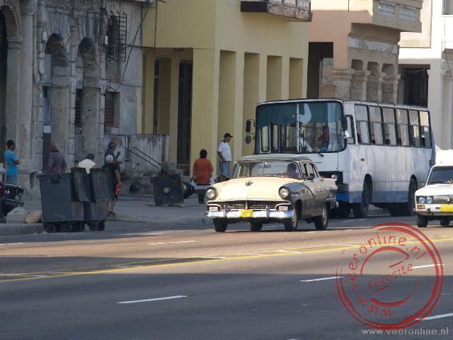 Oude autos rijden over de boulevard van Havana