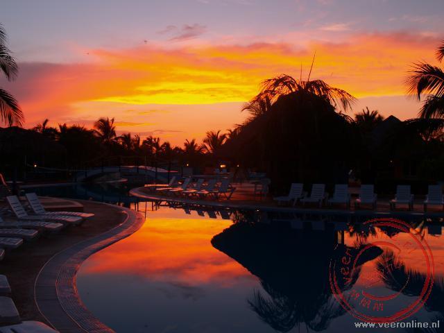 De weerspiegeling van de ondergaande zon in het zwembad