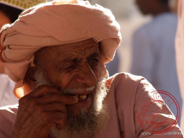 Een Omani man bekijkt het vee op de markt in Nizwa