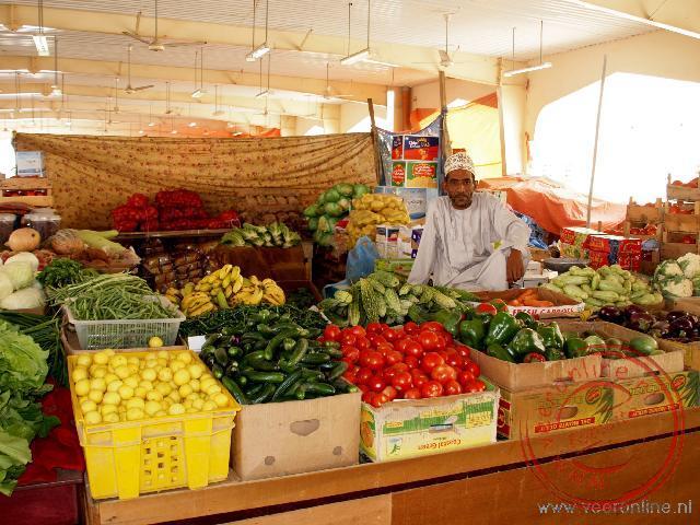 De trotse verkoper op de groente en fruitmarkt van Sinaw