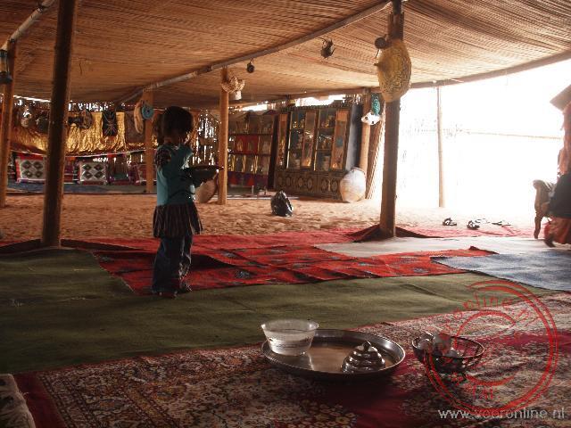 Een meisje deelt de thee uit in de Bedoeïnen tent