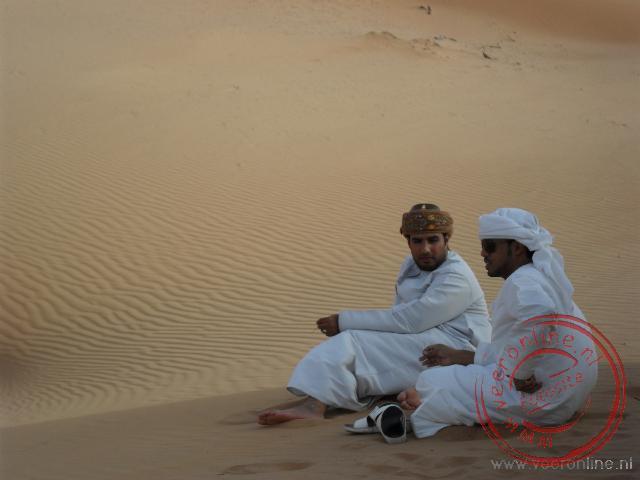 Twee chaufferus wachten in de Wahiba Woestijn