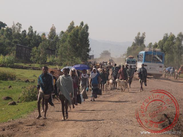 De lokale bevolking loopt langs de weg naar de weekmarkt