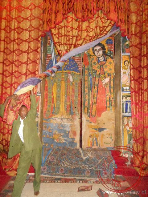 Een klerk houdt het gordijn opzij, zodat de fresco's zichtbaar worden