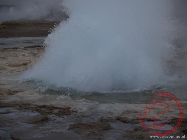 De uitbarsting van geiser Strokkur op het moment dat hij een enorme waterhoeveelheid de lucht in spugt