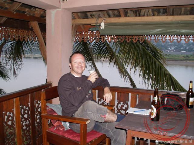 Een biertje op de veranda in Chiang Khong. Op de achtergrond de Mekong rivier. Aan de overzijde Laos