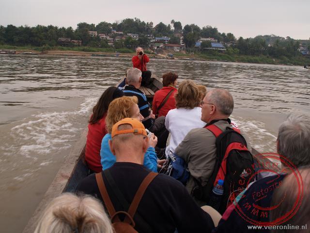 Met een longboat wordt de Mekong Rivier, de grens tussen Thailand en Laos overgestoken