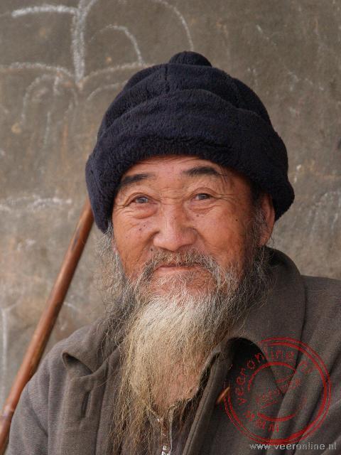 Een oude man in Kiokacham geniet er van als hij op de foto gezet wordt.