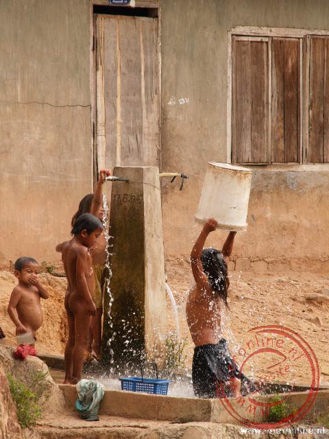 Kinderen wassen zich bij de waterpomp