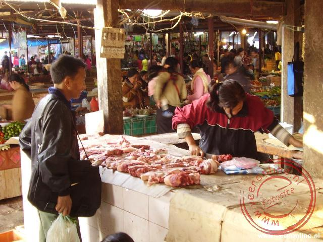 Het vlees wordt gesneden op de markt van Phonsavan