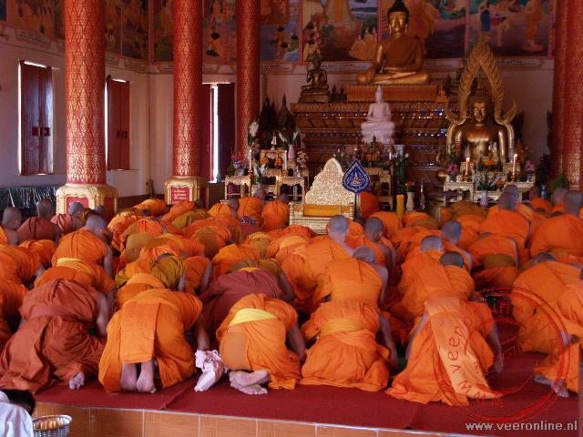 Monniken nemen deel aan het gebed in de Wat That Luang Neua. De tempel naast de Pha That Luang