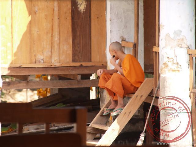 Een monnik scheert zich op e trappen van het Wat Phabat Phonsane