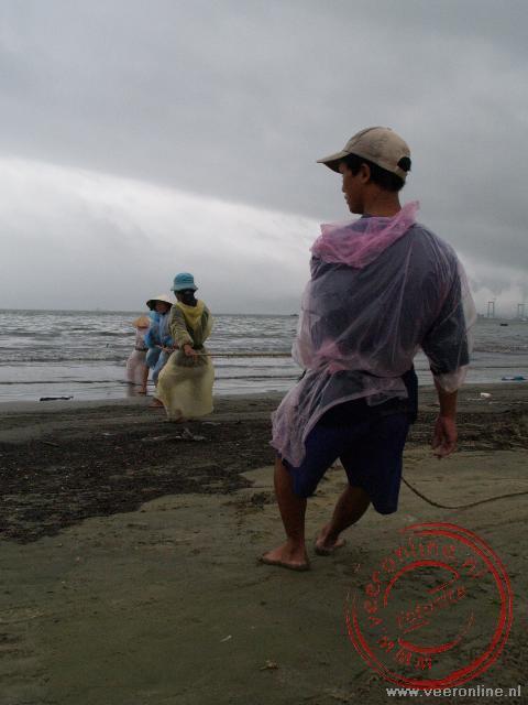 Vissers halen hun netten binnen op het strand