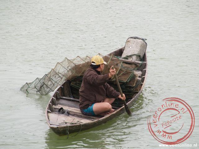 Een visser zet zijn netten uit in de haven van Hoi An