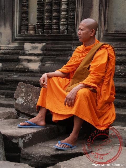 Een monnik zit op een steen in de Angkor Wat