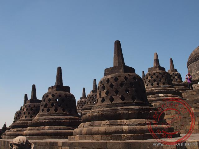 Op de hoogste plateaus staan Boeddha beelden in Stupa s
