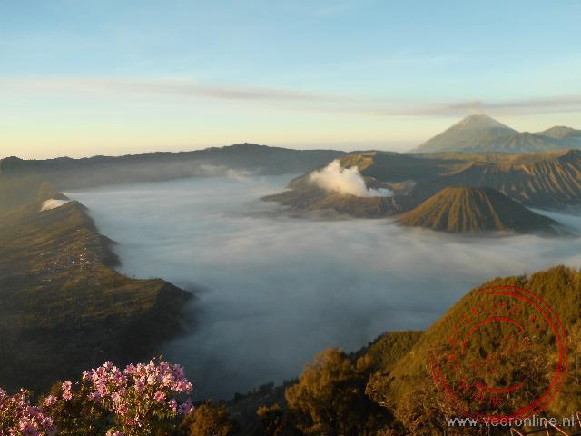 De Bromo vulkaan met laaghangende bewolking in de vallei