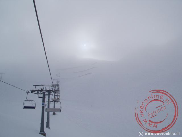 De stoeltjeslift verdwijnt in de mist