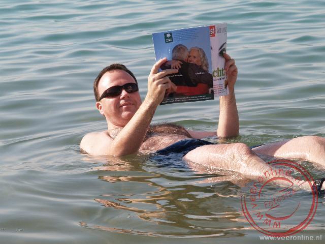 Drijvend een boekje lezen in het mineraal rijke water van de Dode zee