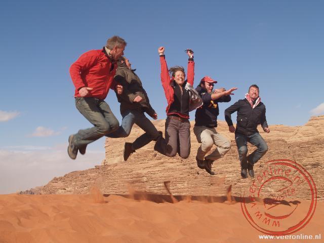 Springen boven op de zandduin in Wadi Rum