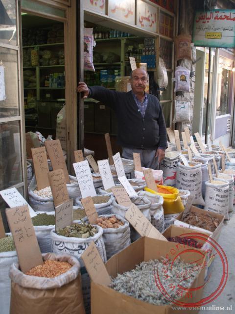 Een trotse eigenaar toont zijn winkeltje in de Souq van Amman