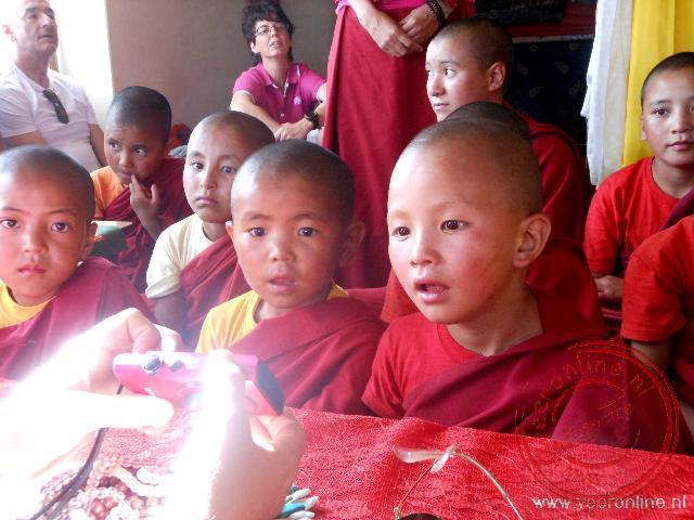 Jonge nonnen kijken vol belangstelling naar de digitale foto's