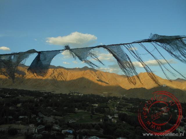 Versleten gebedsvlaggen bij de ondergaande zon in Leh