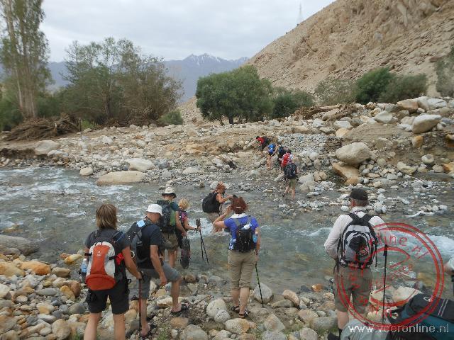 Met slippers passeren we het ijskoude smeltwater tijdens de trekking in Ladakh
