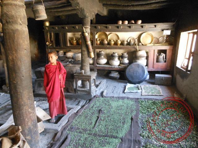 Een jonge monnik toont de oude keuken in het Rizong klooster, nu vooral gebruikt om vruchten te drogen