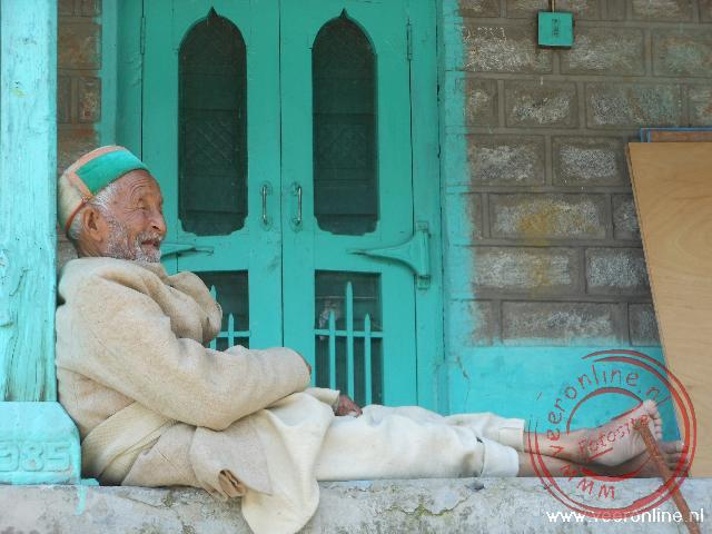 Een oude man rust wat uit in Manali