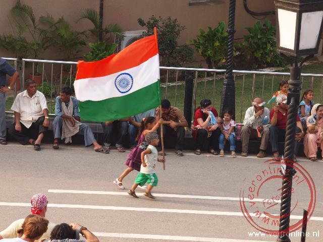 Er klinkt gejuich op als de kinderen voorbij rennen met de vlag