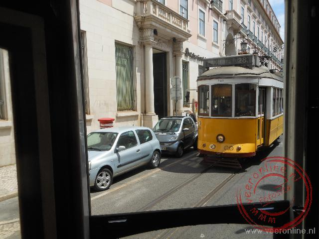 De typische gele tram 28 rijdt over het smalle spoor door de straten