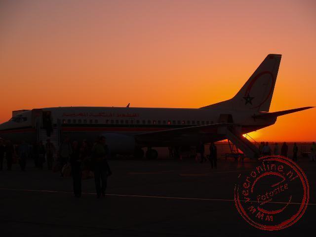 Het vliegtuig op het vliegveld van Agadir met de ondergaande zon