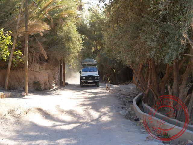 De terreinwagen doet veel stof opwaaien in het dorp